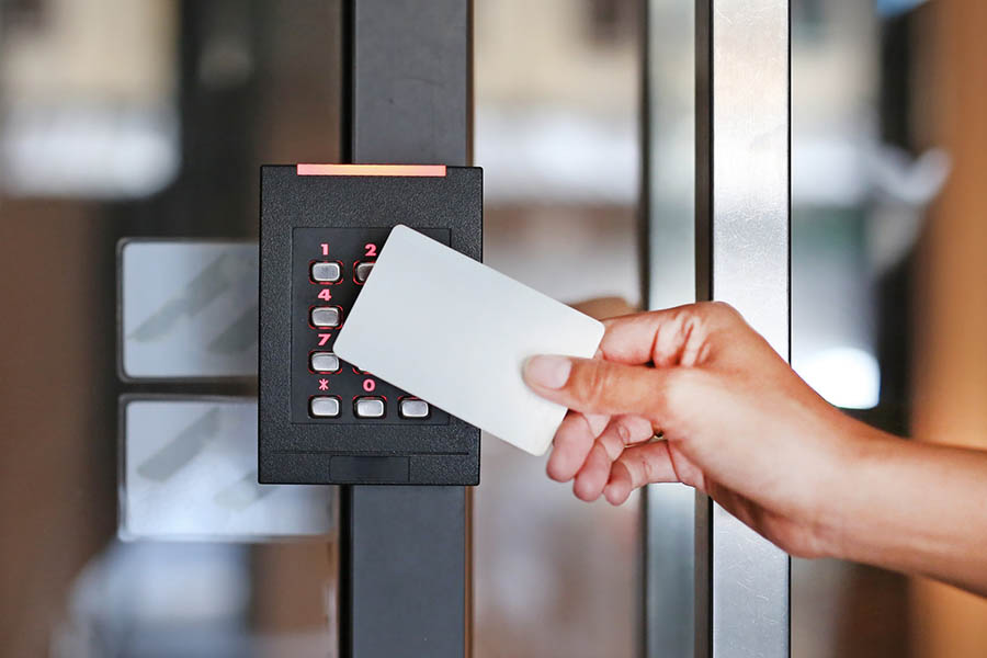 Door access control - young woman holding a key card to lock and